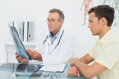Doctor explaining lungs xray to patient in office. Male doctor explaining lungs xray to patient in the medical office stock images