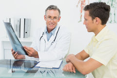 Doctor explaining lungs xray to patient in office. Male doctor explaining lungs xray to patient in the medical office stock photography