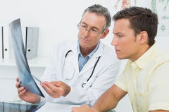 Doctor explaining lungs xray to patient in office. Male doctor explaining lungs xray to patient in the medical office royalty free stock image