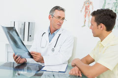 Doctor explaining lungs xray to patient in office. Male doctor explaining lungs xray to patient in the medical office royalty free stock photography