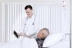 Doctor explaining medical report to elderly patient Royalty Free Stock Images
