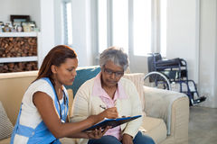 Doctor explaining medication on clipboard to senior woman in living room Stock Photo