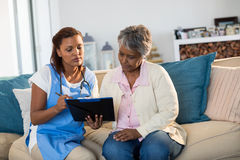 Doctor explaining medication on clipboard to senior woman in living room Royalty Free Stock Photography