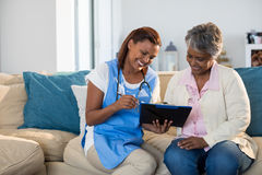 Doctor explaining medication on clipboard to senior woman in living room Stock Image