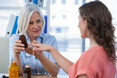 Doctor explaining medicine to her patient Stock Photos