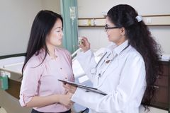 Doctor explaining medicine to her patient. Portrait of doctor explaining bottle of medicine to her patient while standing in the room Royalty Free Stock Photo