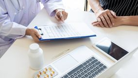 Doctor explaining for patient and showing medical records informations and diagnosis patient symptoms in a consultation and. Medical insurance concept royalty free stock image
