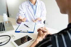 Doctor explaining for patient and showing medical records informations and diagnosis patient symptoms in a consultation and. Medical insurance concept royalty free stock images
