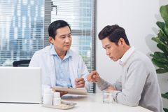 Doctor explaining prescription to male patient, healthcare conce. Pt Royalty Free Stock Images