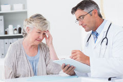 Doctor explaining prescription to senior patient. Doctor explaining prescription to senior female patient in clinic Stock Images