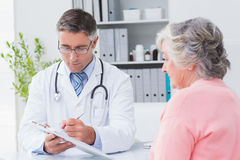 Doctor explaining prescriptions to senior woman Stock Images