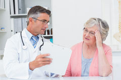 Doctor explaining prescriptions to tensed senior woman Stock Photos