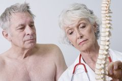 Doctor Explaining The Problems About Spinal Cord To Patient. Senior female doctor explaining the problems about spinal cord to patient in clinic stock photo