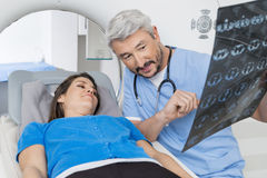 Doctor Explaining X-ray To Patient Lying On CT Scan Machine. Male doctor explaining chest X-ray to female patient lying on MRI scan machine in hospital Stock Photo