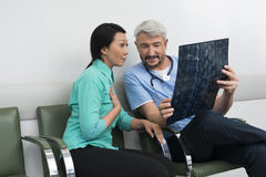 Doctor Explaining X-ray To Surprised Patient royalty free stock photography