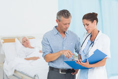 Doctor explaining report to female patient and husband. In the hospital Stock Image