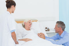 Doctor explaining report to female patient and husband Stock Images