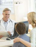 Doctor Explaining Report To Mother And Son In Hospital Royalty Free Stock Photo