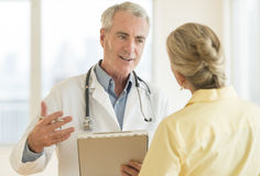 Doctor Explaining Report To Patient In Hospital. Senior doctor with clipboard explaining report to female patient in hospital Stock Image
