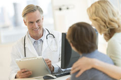 Doctor Explaining Report To Son And Mother At Clinic Stock Photography