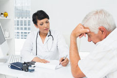 Doctor explaining reports to worried senior patient royalty free stock photography