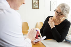 Doctor Explaining Shoulder Rotator Cuff Model To Senior Woman stock images