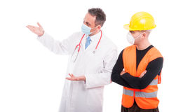 Doctor explaining something to constructor. Wearing marks and protection helmet isolated on white background with copy text space Stock Photo