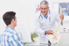 Doctor explaining a spine model to patient Stock Photos