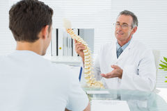 Doctor explaining spine to a patient in office Stock Photos