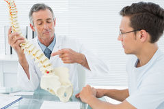 Doctor explaining spine to patient in office Stock Images