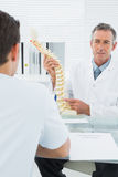Doctor explaining spine to a patient in office Stock Photography