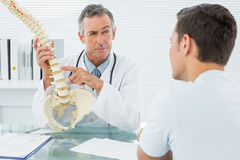 Doctor explaining spine to a patient in office Royalty Free Stock Photography