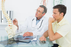 Doctor explaining spine to a patient in office Stock Photo