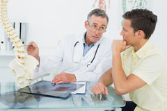 Doctor explaining spine to patient in office Royalty Free Stock Photo