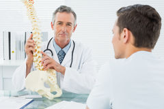 Doctor explaining spine to patient in office Royalty Free Stock Photos