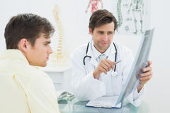 Doctor explaining spine xray to patient in office Royalty Free Stock Images