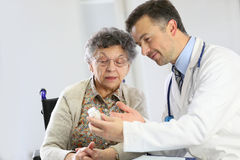 Doctor explaining to an elderly woman the use of medications Stock Image