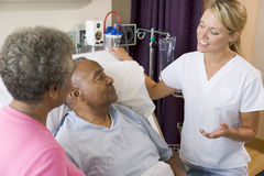 Doctor Explaining To Senior Couple. In Patients Room royalty free stock photos