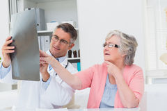 Doctor explaining x-ray to senior patient Stock Image