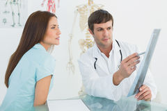 Doctor explaining xray to female patient in the medical office Stock Image