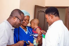 Caregivers and their patients. The doctor explains something to the baby`s father while the nurse holds the baby in her arms stock images
