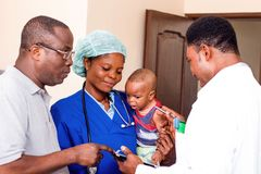 Caregivers and their patients. The doctor explains something to the baby`s father while the nurse holds the baby in her arms stock image