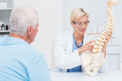 Doctor explaning anatomical spine to senior patient Stock Photography