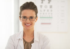 Doctor in eyeglasses in front of snellen chart. Doctor woman in eyeglasses in front of snellen chart Royalty Free Stock Images