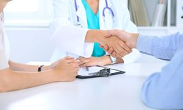 Doctor and family couple of patient are discussing something, just hands at the table. Medicine concept.  stock image
