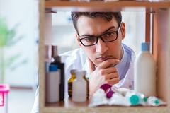 The doctor at farmacy retail shop looking for medicines. Doctor at farmacy retail shop looking for medicines Stock Photography