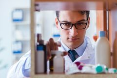 The doctor at farmacy retail shop looking for medicines. Doctor at farmacy retail shop looking for medicines Stock Images