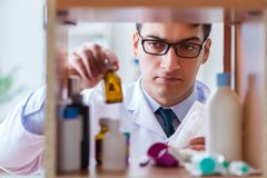 The doctor at farmacy retail shop looking for medicines. Doctor at farmacy retail shop looking for medicines Stock Photo