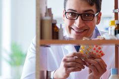 The doctor at farmacy retail shop looking for medicines. Doctor at farmacy retail shop looking for medicines Stock Image