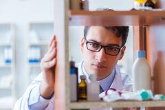 The doctor at farmacy retail shop looking for medicines. Doctor at farmacy retail shop looking for medicines Royalty Free Stock Photography